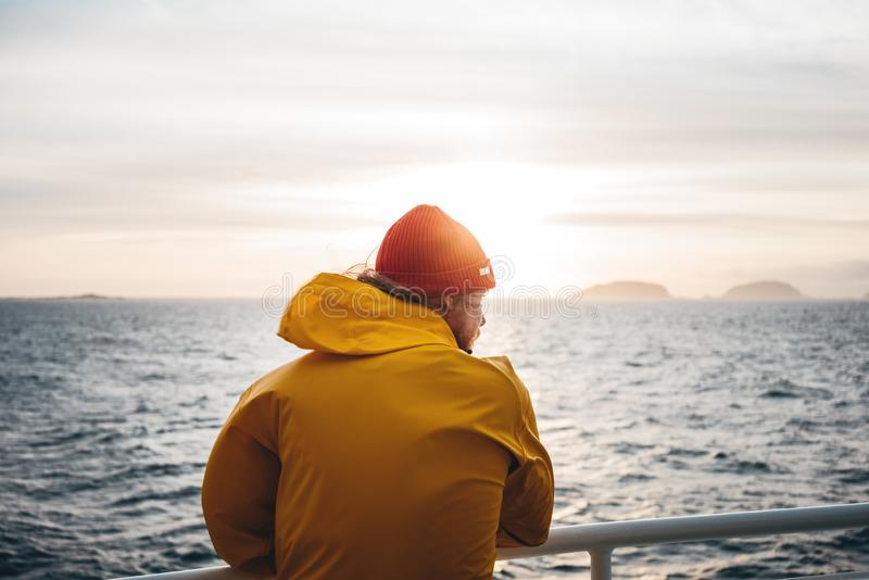 Young traveler wearing red hat and yellow raincoat floating on ship looking at sunset sea after storm and foggy mountains on skyli. Ne. Lifestyle travel royalty free stock photography