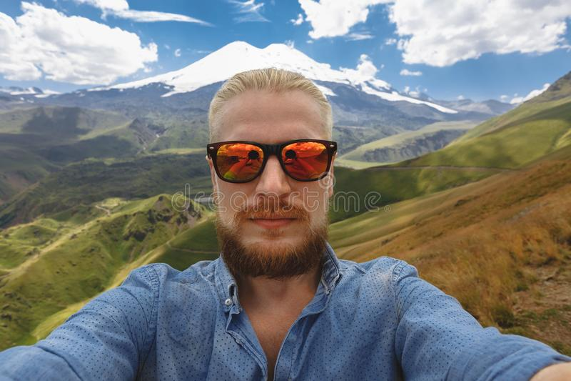 Young Traveler Man Makes Selfie On Background Of Mount Elbrus. Adventure Destination Journey Concept stock photography