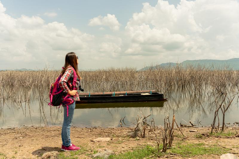 Young woman staying on the lake in summer time stock photography