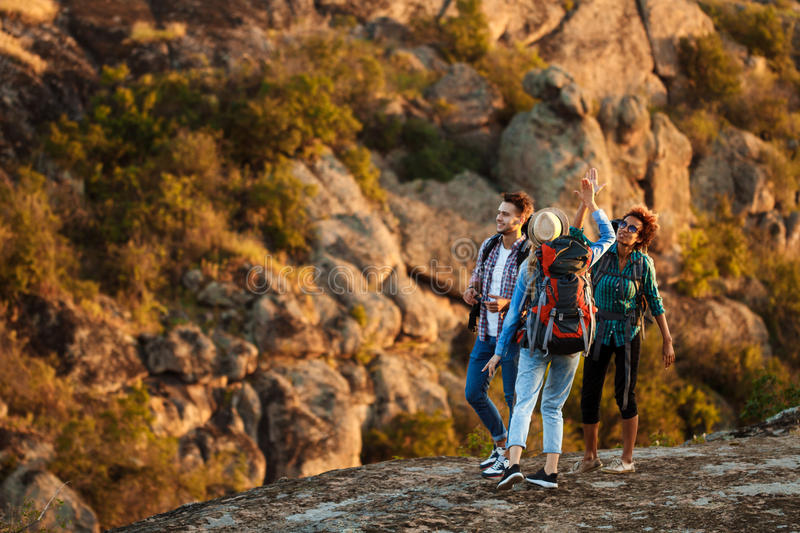 Young travelers with backpacks smiling, giving highfive, walking in canyon. royalty free stock images