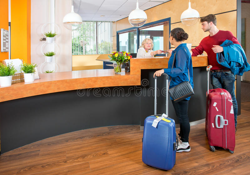 Young travelers at hotel check in. Young couple at the check in counter of a hotel, having just arrived with their luggage from the airport stock image