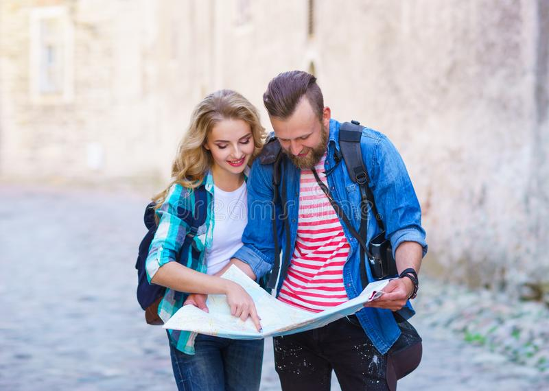 Young travelers with a tourist map. Man and woman having vacation. Backpackers, traveling and tourism concept. royalty free stock images