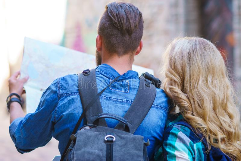 Young travelers with a tourist map. Man and woman having vacation. Backpackers, traveling and tourism concept. royalty free stock photography