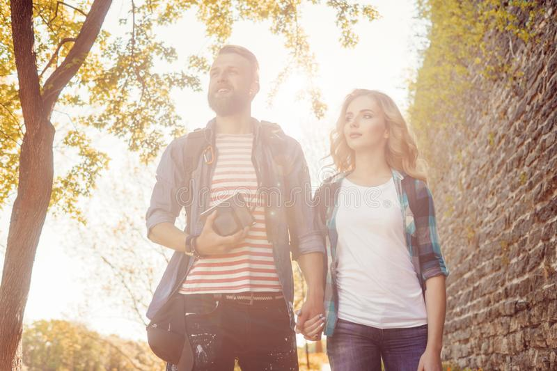 Young travelers walking in autumn park. Man and woman having vacation. Backpackers, traveling and tourism. royalty free stock photography