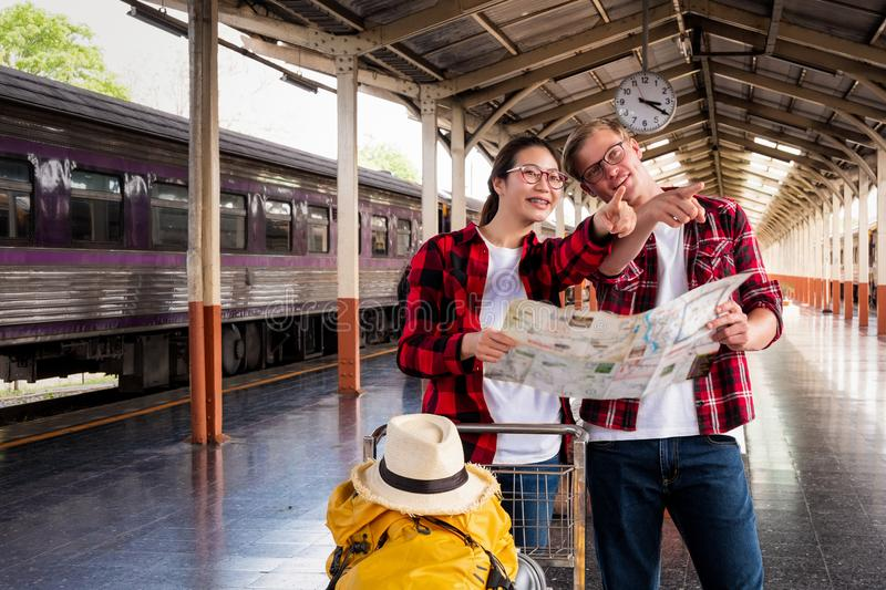 Young traveling backpacker on vacation use map at the train stat. Young traveling backpacker vacation use map at train station stock image