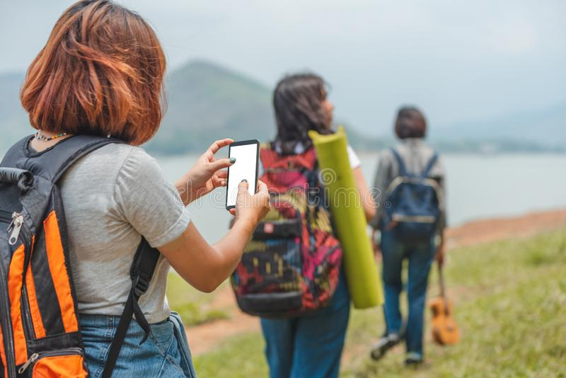 Young traveller woman in jungle planning trip with map and smartphone. Travel and active lifestyle concept stock photos