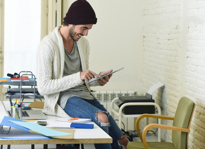 Young trendy businessman in beanie and cool hipster informal look sitting on home office desk using digital tablet pad happy. Young trendy businessman in beanie royalty free stock photos