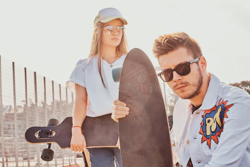 Young trendy couple is chilling on the sunny street with their longboards royalty free stock images