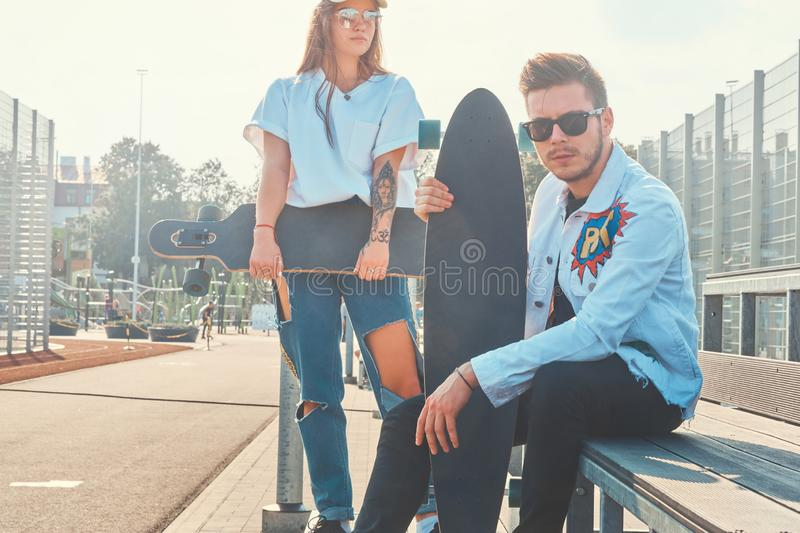 Young trendy couple is chilling on the sunny street with their longboards stock image