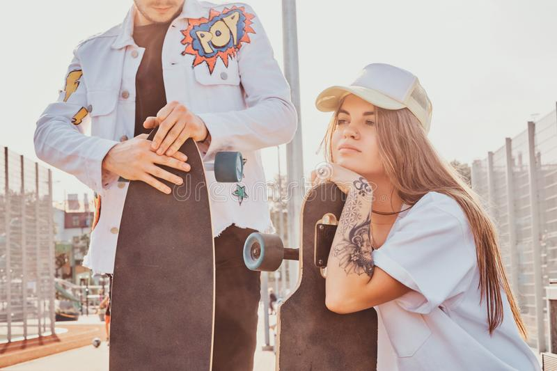 Young trendy couple is chilling on the sunny street with their longboards stock photo