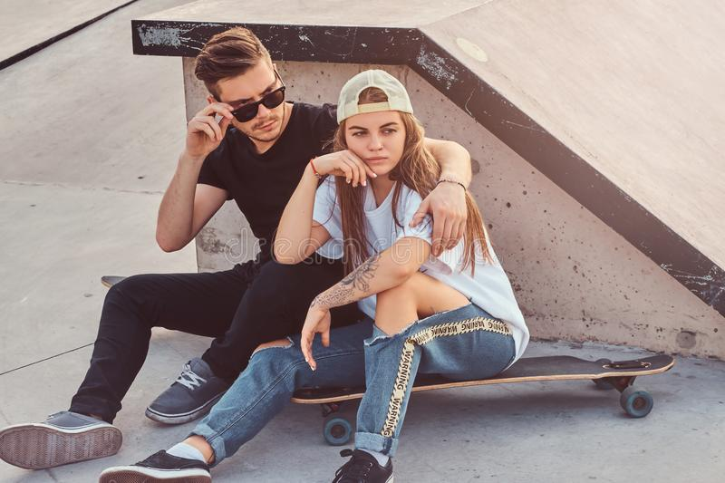Young trendy couple is sitting at sunny skatepark with their longboards stock photos