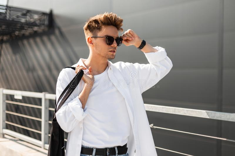 Young trendy hipster man with a stylish hairstyle straightens black sunglasses. Handsome modern guy in fashionable white clothes. With a cloth bag posing on a royalty free stock image