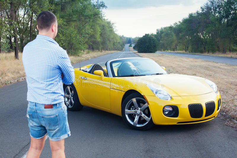 Young trendy male driver. Looking his convertible yellow car royalty free stock images