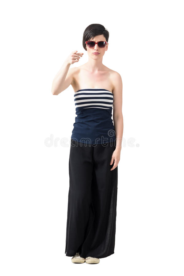 Young trendy short hair woman wearing sunglasses pointing finger at camera. Full body length portrait isolated over white studio background stock image