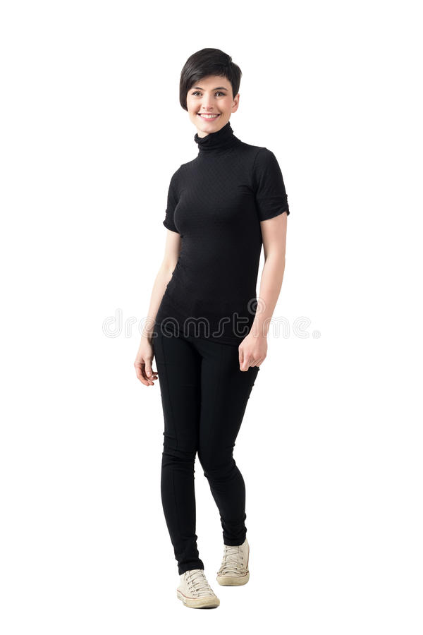 Young trendy slim short hair woman in black turtleneck t-shirt and pants smiling at camera. Full body length portrait isolated over white studio background royalty free stock photography