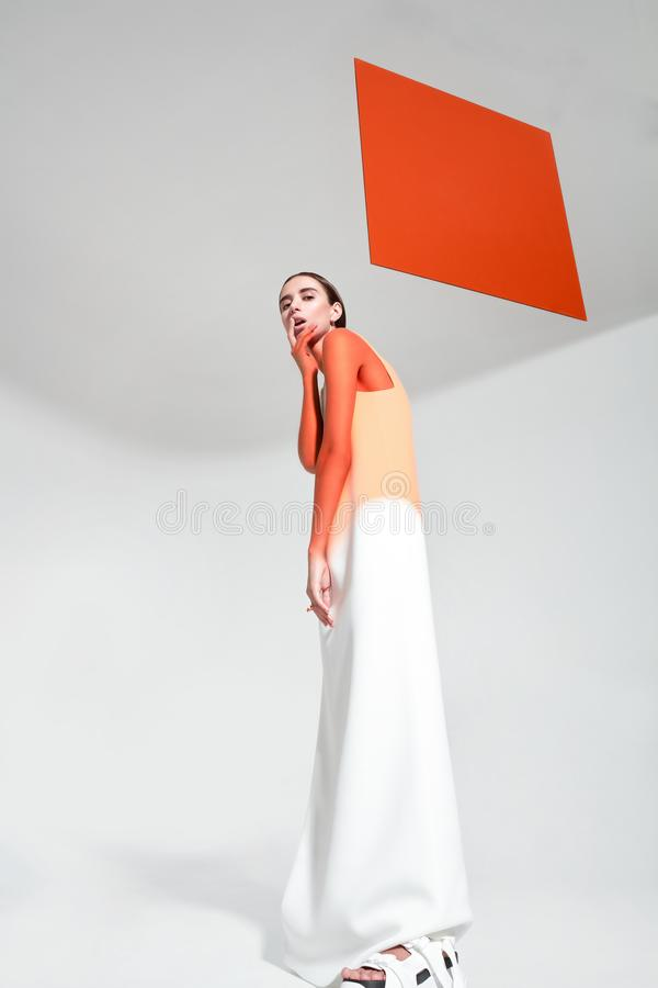 Young trendy woman with orange limelight square behind royalty free stock photos