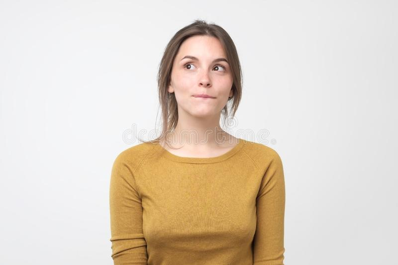 Young tricky woman having something in mind with sly facial expression royalty free stock photo
