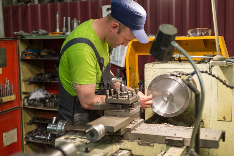 A young turner processes a metal workpiece on a mechanical lathe. royalty free stock image