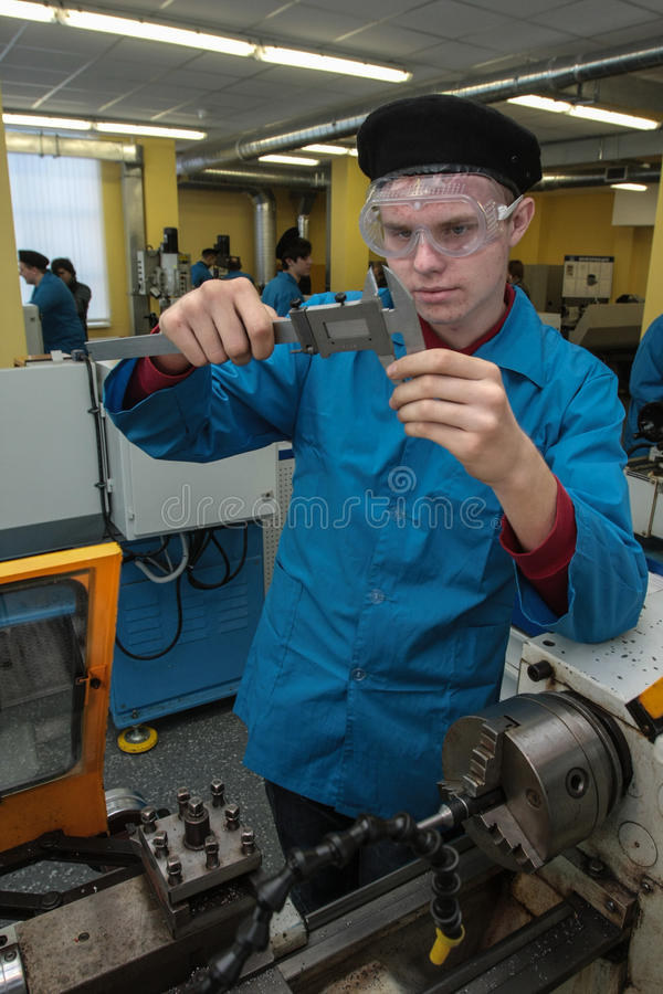Young turner works on a lathe royalty free stock photos
