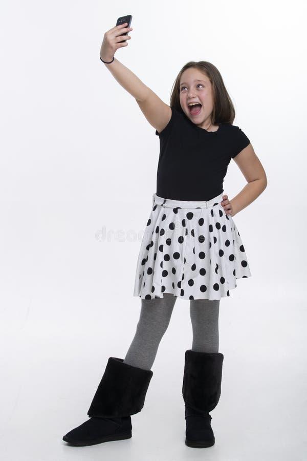 Young Tween Girl Kneeling On A Dock. Stock Image - Image