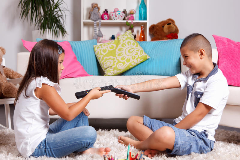 Young twins arguing about watching TV. Young twin siblings arguing about the remote control stock images