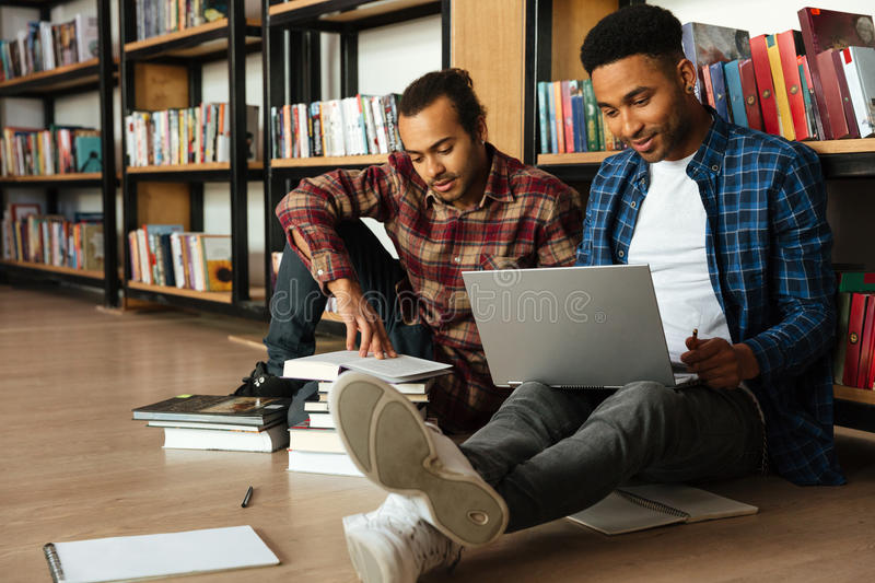 Young two african men reading books using laptop computer stock photography