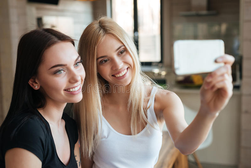 Young two happy women sitting at home indoors make selfie royalty free stock photography
