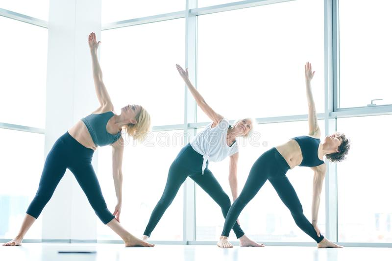 Activity in gym. Young and two mature active barefoot women in sportswear doing side-bend exercise in modern fitness center stock photo