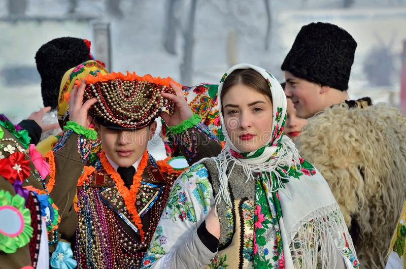 Young ukrainian man and woman perform Malanka song during ethnic festival in open-air museum of folk architecture,Bukovina royalty free stock image