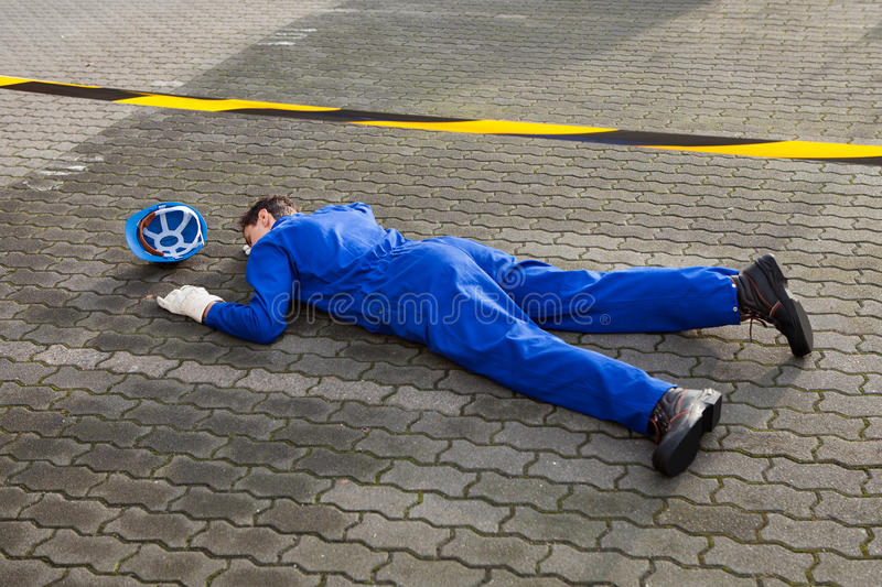 Young unconscious technician lying on street. Full length of young unconscious technician lying on street royalty free stock photos