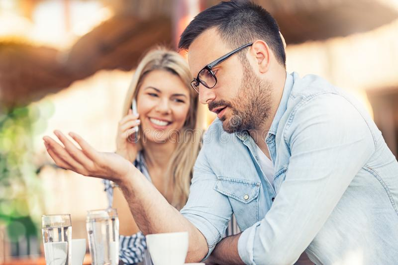 Young unhappy man and his girlfriend who uses the phone royalty free stock photo