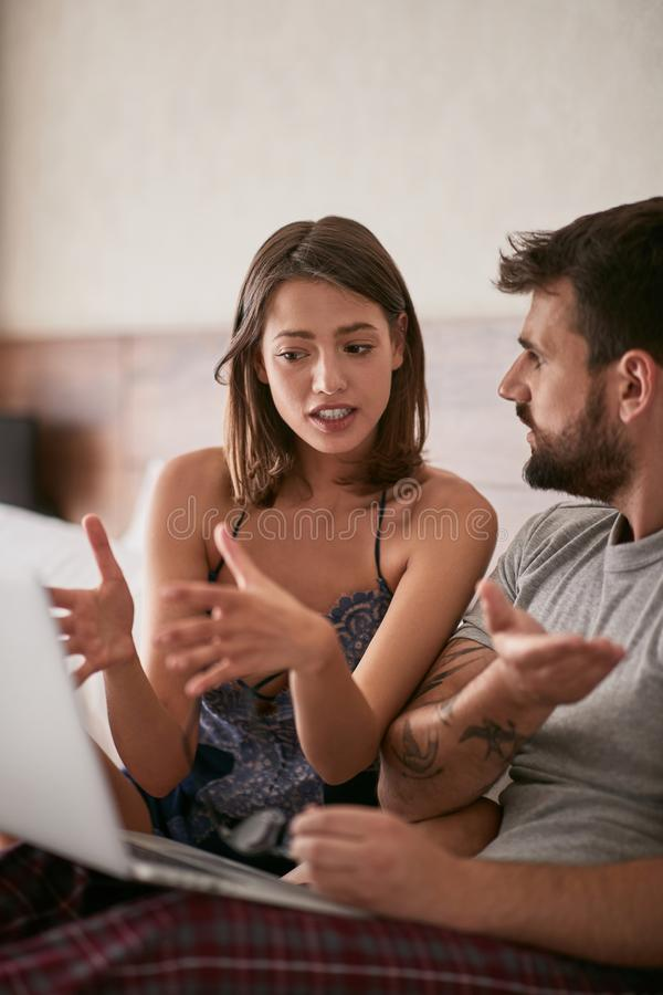 Unhappy Man and woman discussion in the bed with laptop and surf stock image