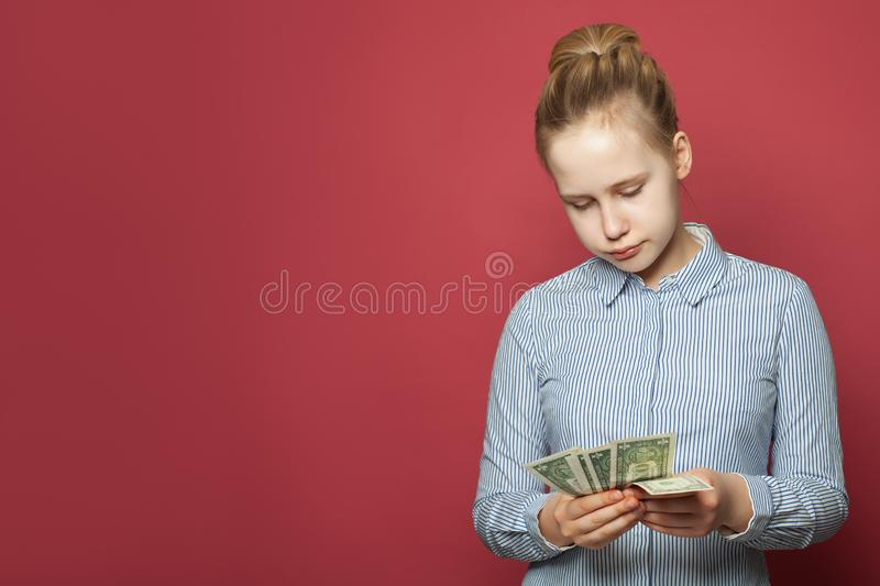 Young  unhappy puzzled girl holding one us dollars cash money on pink background stock photos