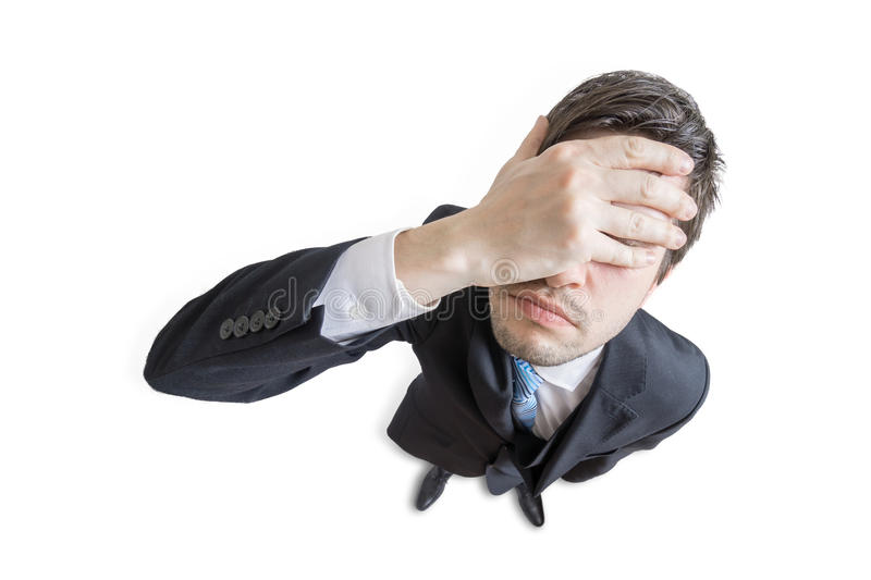 Young unhappy and stressed man made mistake and is covering his face with hand. Isolated on white background. View from top stock image