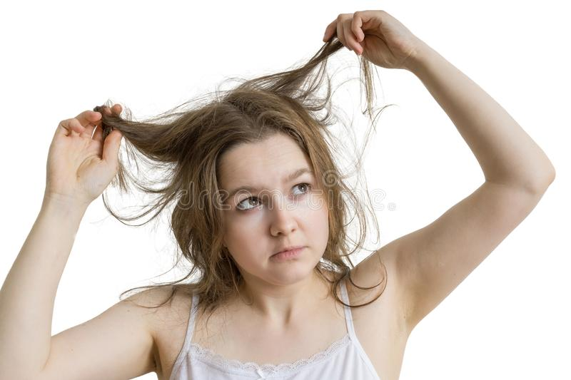 Young unhappy woman is looking at her damaged and dry hair. Isolated on white background royalty free stock image