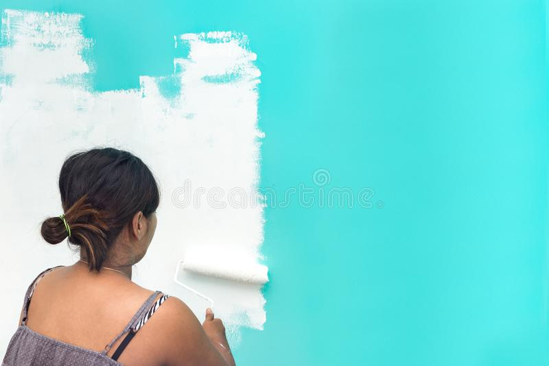 Young unidentifiable Asian woman painting wall with paint roller stock photography
