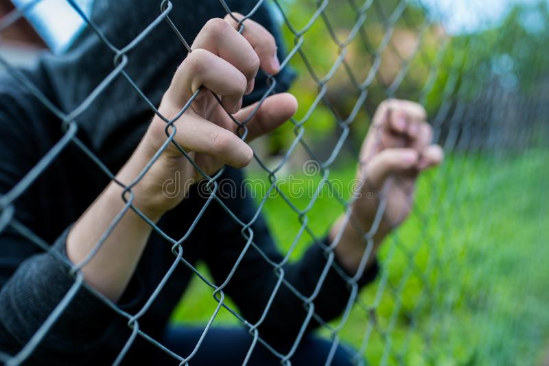Young unidentifiable teenage boy holding the wired garden at the correctional institute, conceptual image of juvenile delinquency,. Focus on the boys hand stock photo