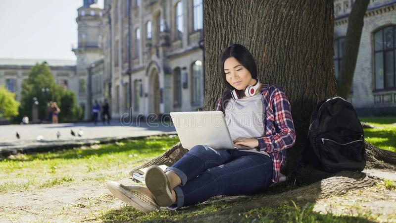 Young university student using laptop with smile on face, sitting under tree stock image