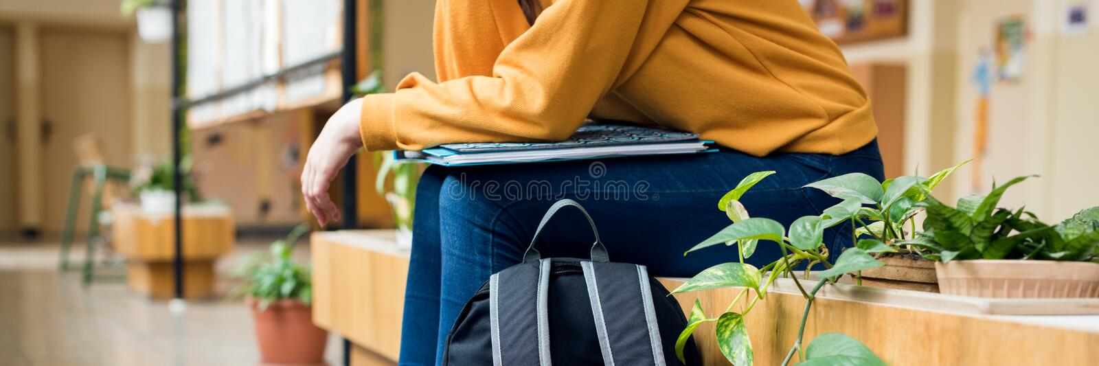Young unrecognisable depressed lonely female college student sitting in the hallway at her school. Education, Bullying, Depression royalty free stock photo