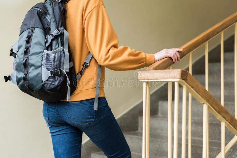 Young unrecognisable depressed lonely female college student walking up the stairs at her school. stock photography