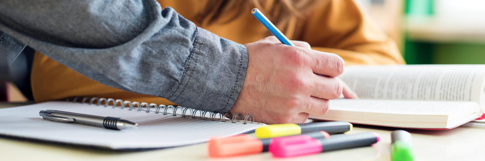 Young unrecognisable teacher helping his student in class. Education, Tutoring and Encouragement. stock photo