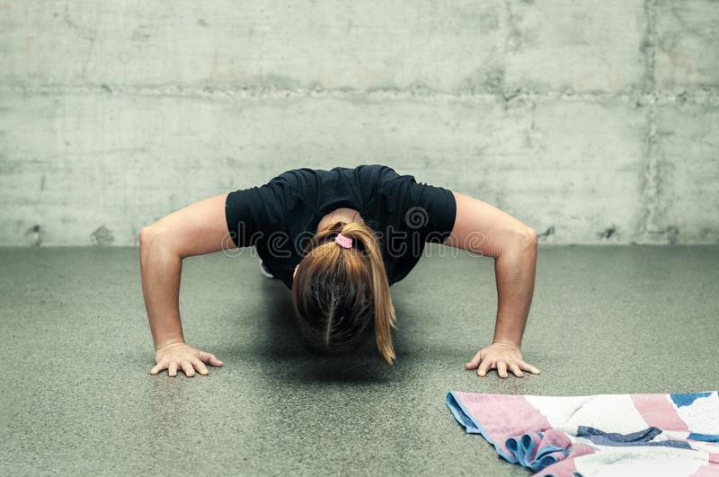 Young unrecognizable attractive fitness girl push ups training workout on the gym floor.  royalty free stock photography