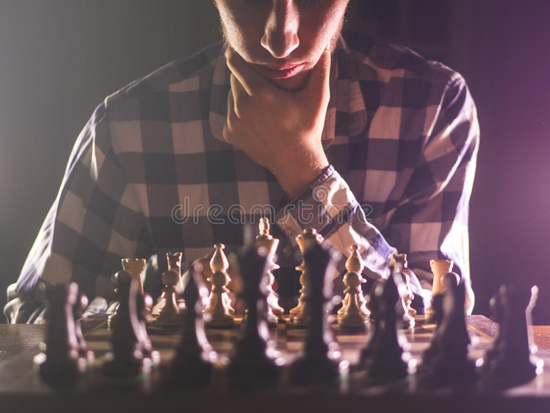 Young unrecognizable male person thinking near chess board concept with dark background royalty free stock image
