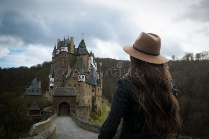 Young unrecognizable woman walks along the road leading to a incredible castle stock photo