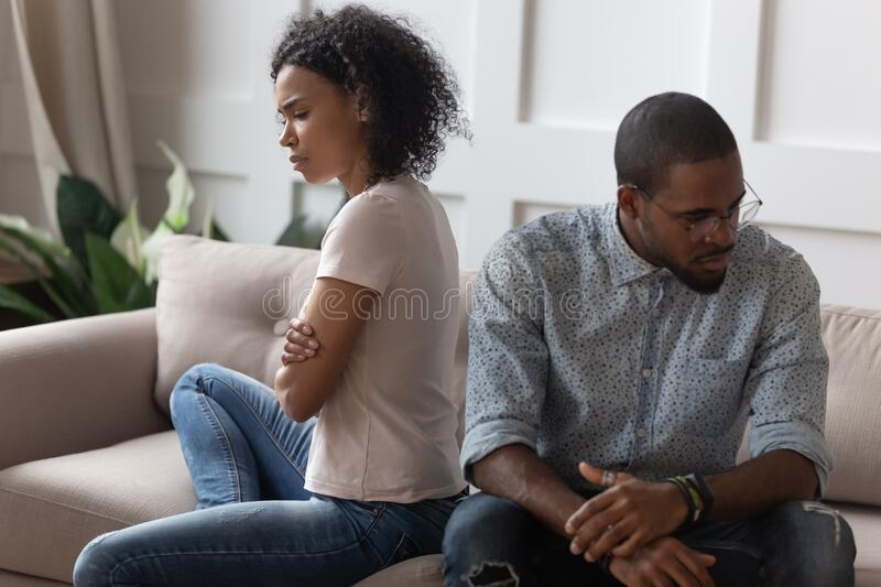 Young unsatisfied family spouse having problems in relations. Upset depressed african american married couple sitting on sofa with crossed hands at silence stock images