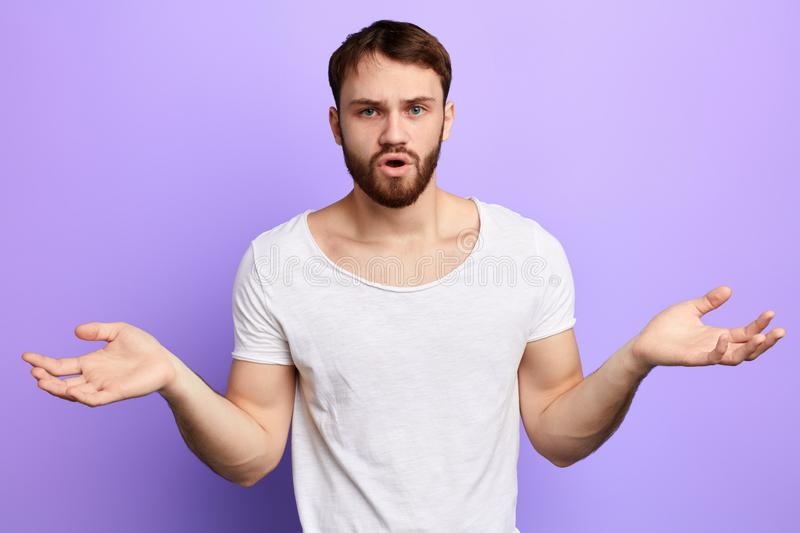 Young unshure puzzled man spreading arms royalty free stock images
