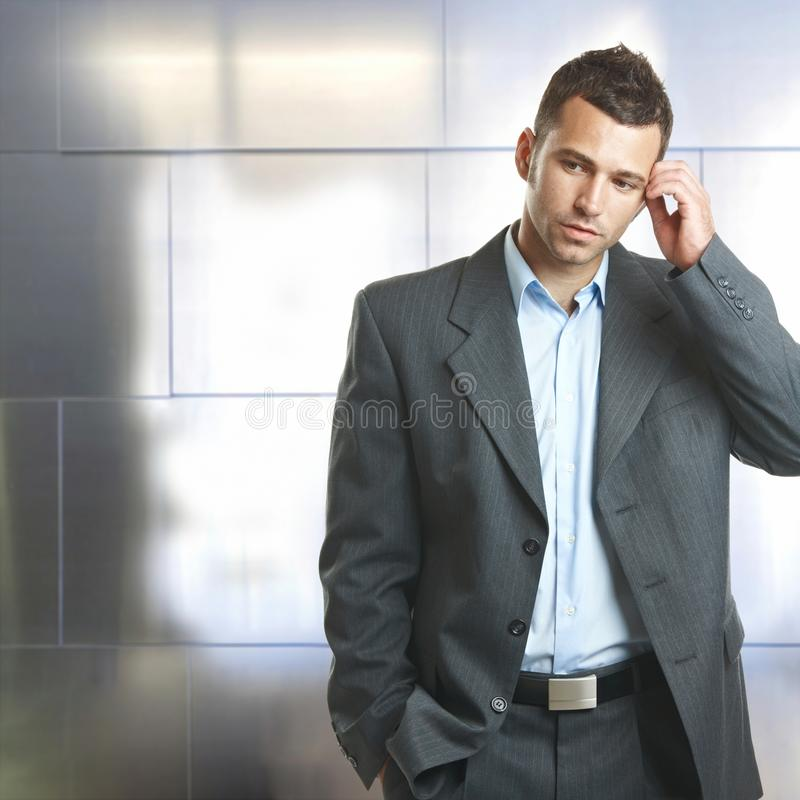 Young unsure businessman standing in front of wall. Young unsure caucasian businessman in suit standing and thinking in front of business office wall. Scratching royalty free stock photo