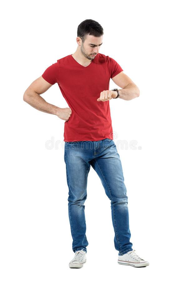 Young upset casual man waiting for someone checking time on wrist watch. Full body length portrait isolated over white studio background royalty free stock images