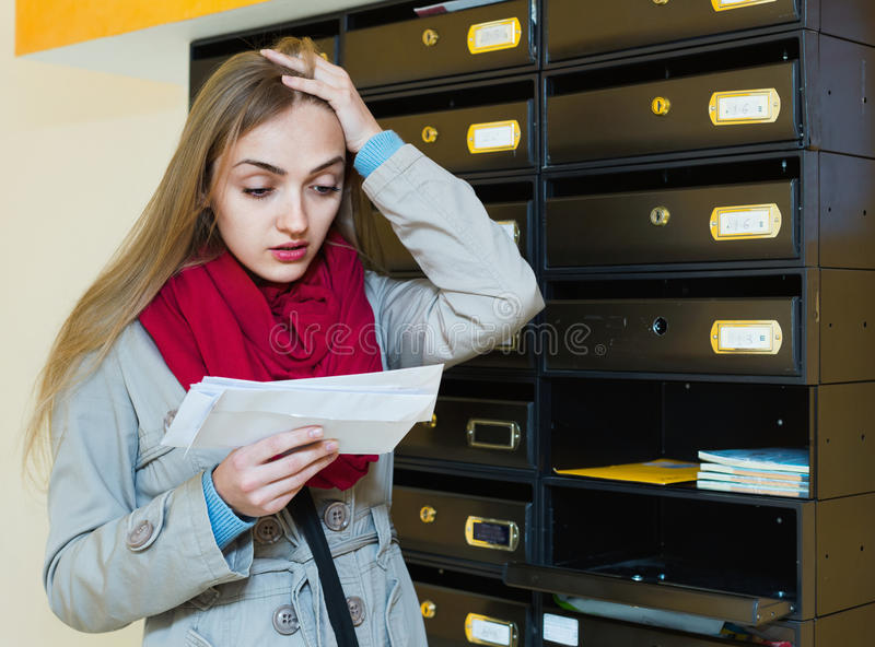 Young upset woman in coat receiving ugly news. By post stock image