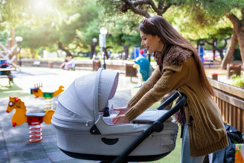 Mother cheering her baby in the pram outdoors in the park. Young urban city mother cheering her baby in the pram outdoors on the playground in the park royalty free stock images